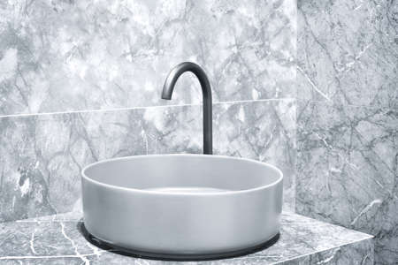 Luxury faucet mixer on a round bowl sink in a beautiful gray marble bathroom