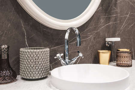Luxury modern big white faucet mixer on a round sink in a beautiful beige marble bathroom, a large round mirror