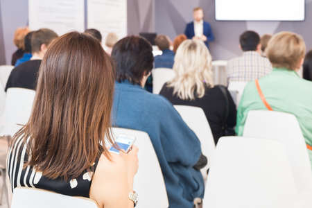 Business woman with a smartphone in hand and people Listening on The Conference. Horizontal Image Standard-Bild - 122469728
