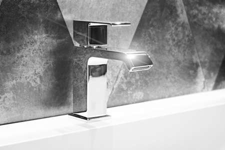 Luxury modern style faucet mixer on a white sink in a beautiful gray  metallic style bathroom Фото со стока