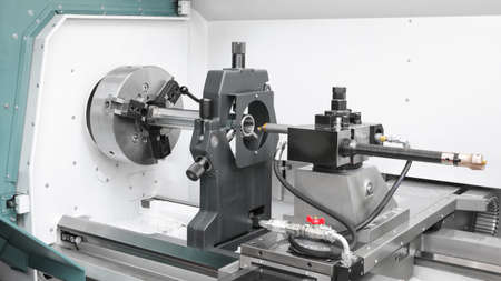 metalworking cnc industry: cutting steel metal shaft processing on lathe machine in workshop.