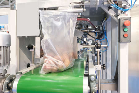 Food factory automated robotic machine. Conveyor product line for cooking and packing rations and food packs. packing potatoes in a plastic bag