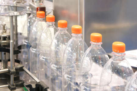 Bottle. Industrial production of plastic pet bottles. Factory line for manufacturing polyethylene bottles. Transparent food packaging