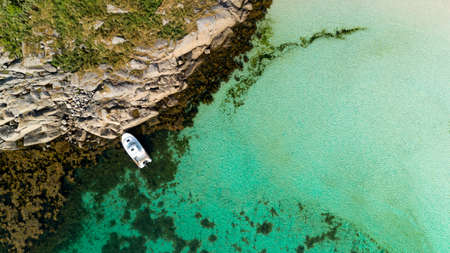 aerial drone view from the top to the blue lagoon with azure sea water with a sandy beach and a yacht Imagens