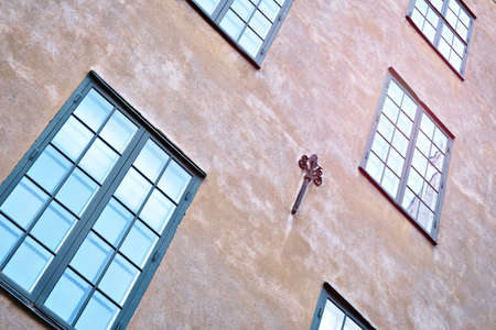 Part of the facade of a red historic building illuminated, reflecting off window panes, in the Old Town Gamla Stan of Stockholm, Sweden. Series - streets of old stockholm
