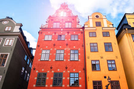 Part of the facade of a red brown historic building illuminated, reflecting off window panes, in the Old Town Gamla Stan of Stockholm, Sweden. Series - streets of old stockholm