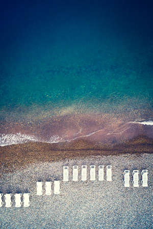 Vacation and travel concept. Aerial view of pebbles beach with colorful umbrellas, bay with transparent blue water at sunset in summer. Top view. Landscape