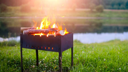 Barbecue Grill. Fire flame on green grass background. Barbecue Grill with Fire on Open Air. Fire flame.