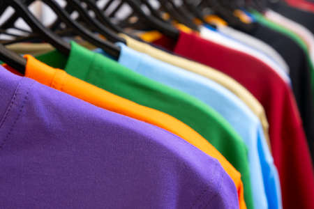 Colorful t-shirts on hangers, close up view 스톡 콘텐츠