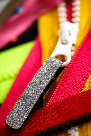 Zip background texture of zippers sliders. a lot of zippers in different colors. sewing clothes, atelier, fabric and accessories shop. hobby diy concept