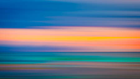 Vivid twilight sunset sky and motion blur of the sea under with long exposure effect. 免版税图像