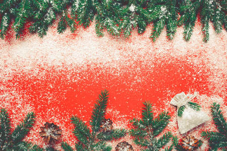 Christmas red background with snow fir tree. Top view with copy space for your text