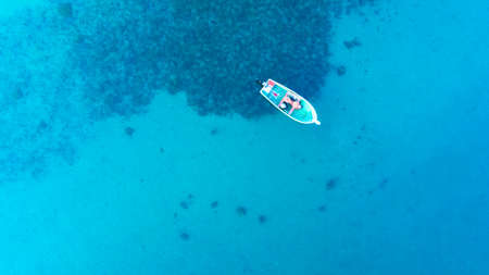 aerial drone view from the top to the blue lagoon with azure sea water with a boat with copy space, vacation concept