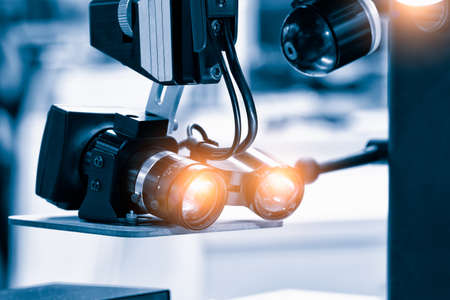 Close up photo of metallic eye piece lens, White optical microscope keep sterile in operating laboratory room. Medical science biology device technology equipment for pharmaceutical research concept.