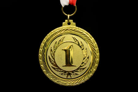 Gold medal, black background, horizontal photo
