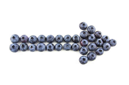 eat right: Arrow made of blueberries isolated on white Stock Photo