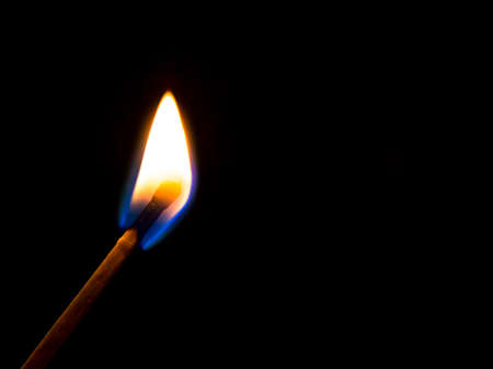 Silhouette of a burning match over black background