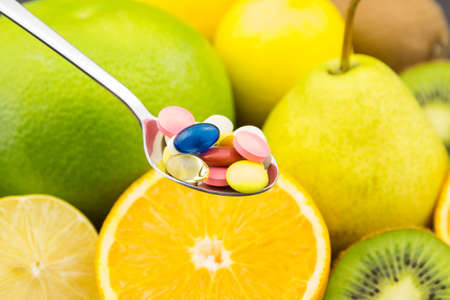 Spoon full of colorful pills photo