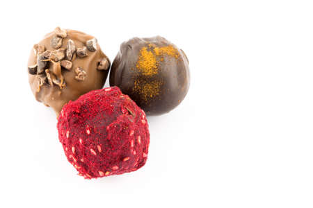 champagne truffles chocolate: Chocolate pralines with almond, honey, brandy liqueur and raspberry powder isolated on white background