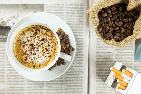 Cup of coffee, roasted beans and pack of cigarettes arranged on a newspaper photo