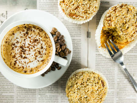 Cup of coffee, roasted beans and muffins arranged on a newspaper photo