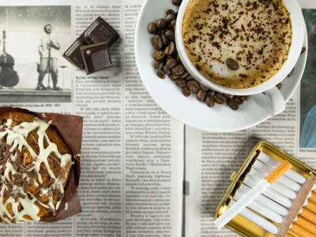 Cup of coffee, chocolate muffin and cigarettes arranged on a newspaper photo
