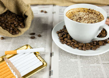 Cup of coffee, roasted beans and cigarettes arranged on a newspaper photo
