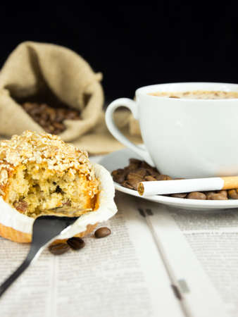 Cup of coffee, muffin and a  cigarette arranged on a newspaper photo