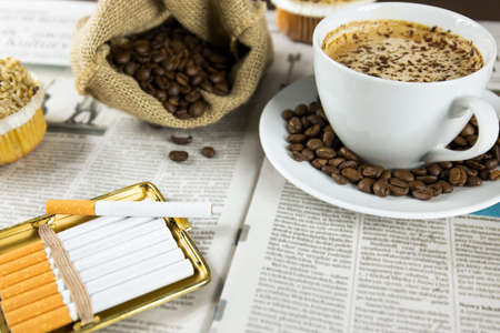 Cup of coffee, muffins and roasted beans arranged on a newspaper photo
