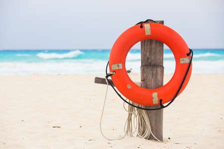 Life buoy attached to a wooden post at the beach in Mexico photo