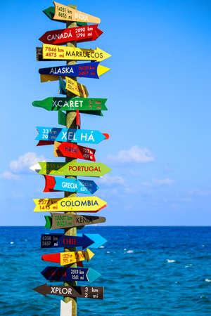 flechas direccion: Divertido señal de dirección con distancia de muchos países diferentes en la costa mexicana