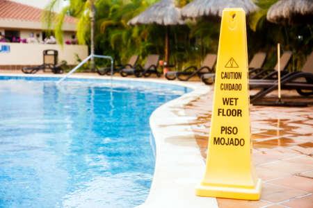 Muestra mojada del suelo de la advertencia en una piscina en México Foto de archivo