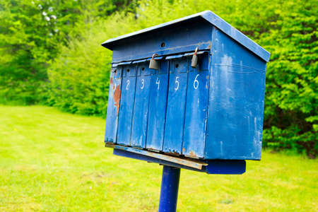 addressee: Old blue mailbox on a stake somewhere  in the country