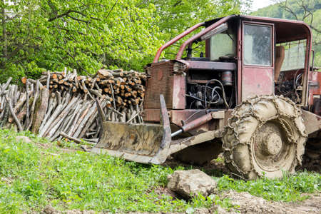 Old bulldozer and wooden bales in a forest photo