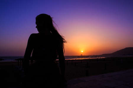 Beautiful sunset and silhouette of a woman in Agadir, Morocco photo