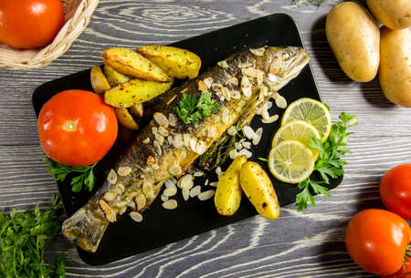 Fried trout with almonds, dill and potato wedges Foto de archivo