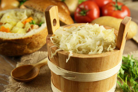 Sauerkraut in a wooden barrel and cabbage soup in the background photo
