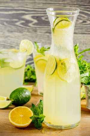Refreshing lemonade drink and ripe fruits against wooden background