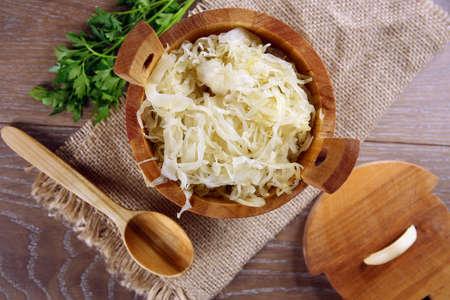 Sauerkraut in a wooden barrel on brown table