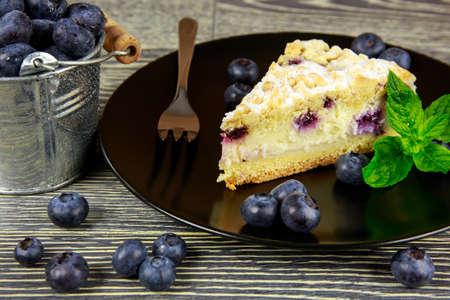 Blueberry cake and fresh fruits arranged on a wooden table photo
