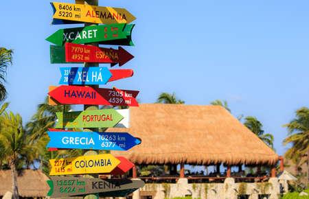 flechas direccion: Divertido poste indicador de dirección con la distancia a muchos países diferentes en la costa mexicana