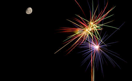 Colorful fireworks against black sky background and moon