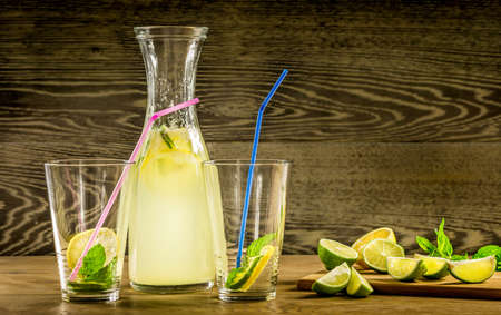 Refreshing lemonade drink and ripe fruits against wooden background photo