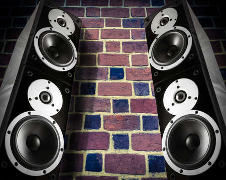 two party system: Black high gloss music speakers on brick wall Stock Photo