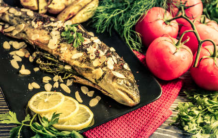 buch: Fried trout with almonds, dill and potato wedges Stock Photo