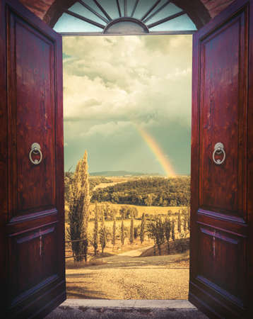 view of a wooden doorway: Old open door and rural landscape with rainbow