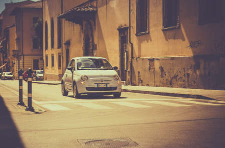 cross roads: AREZZO, ITALY - JUNE 26, 2015: A new version of Fiat 500, one of the most popular small city cars in Italy, on cross roads in tuscan Arezzo city, Italy