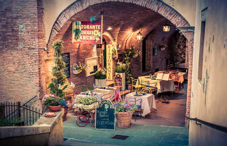 june 25: MONTEPULCIANO, ITALY - JUNE 25, 2015: small pizza restaurant with beautiful flowers decoration in antique Montepulciano city, Italy Editorial