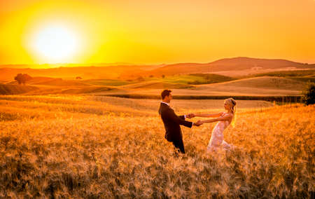 PIENZA, ITALY - JUNE 27, 2015: anonymous newlyweds during photo session on tuscan fields near historic Pienza town