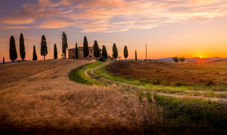 Tuscan sunrise landscape with farmhouse and cypress trees